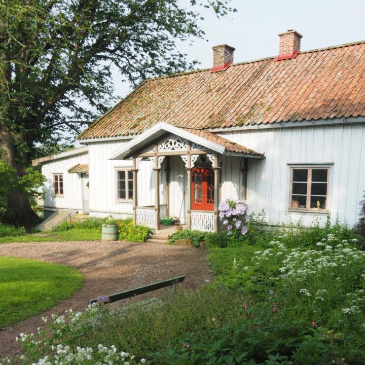 Wit houten boerderijtje met rode deur