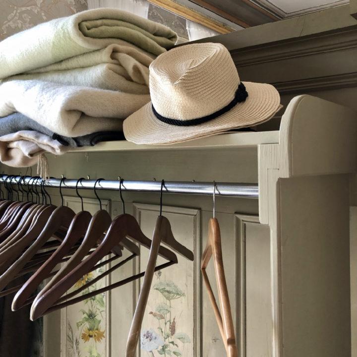 Hoed en stapel dekens bij de garderobe