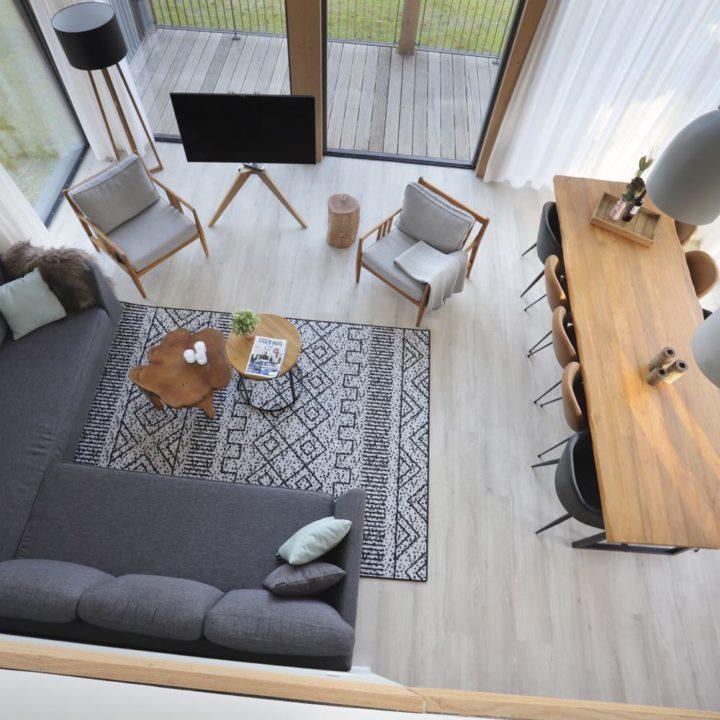 Woonkamer vanaf boven gezien, met grijze hoekbank en lange eettafel