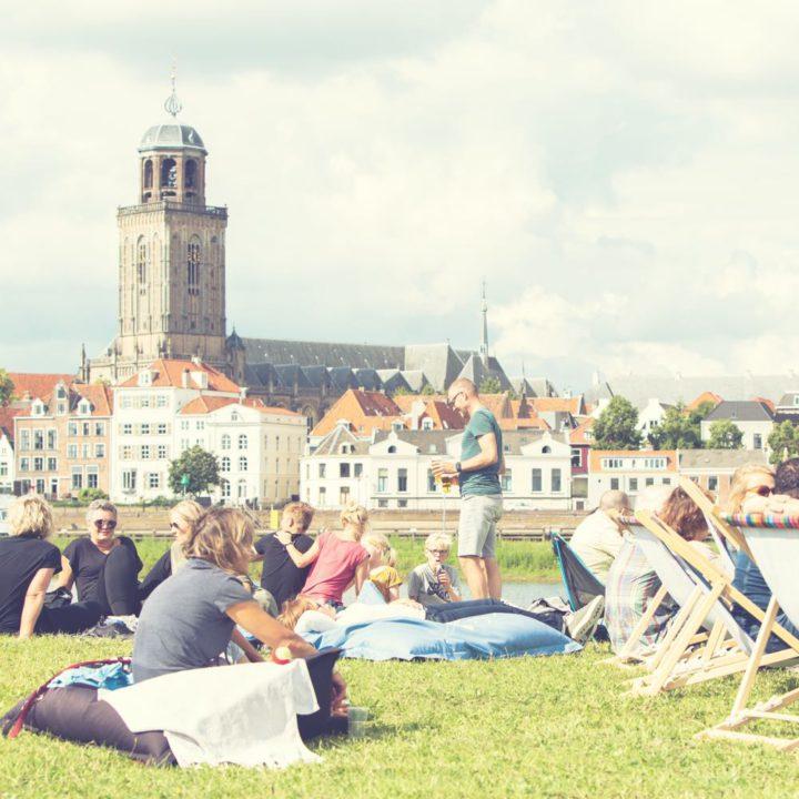 Mensen in het gras op zitzakken en in ligstoelen
