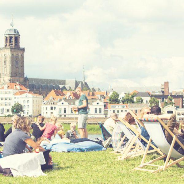Stadsstrand met mensen in het gras en in ligstoelen
