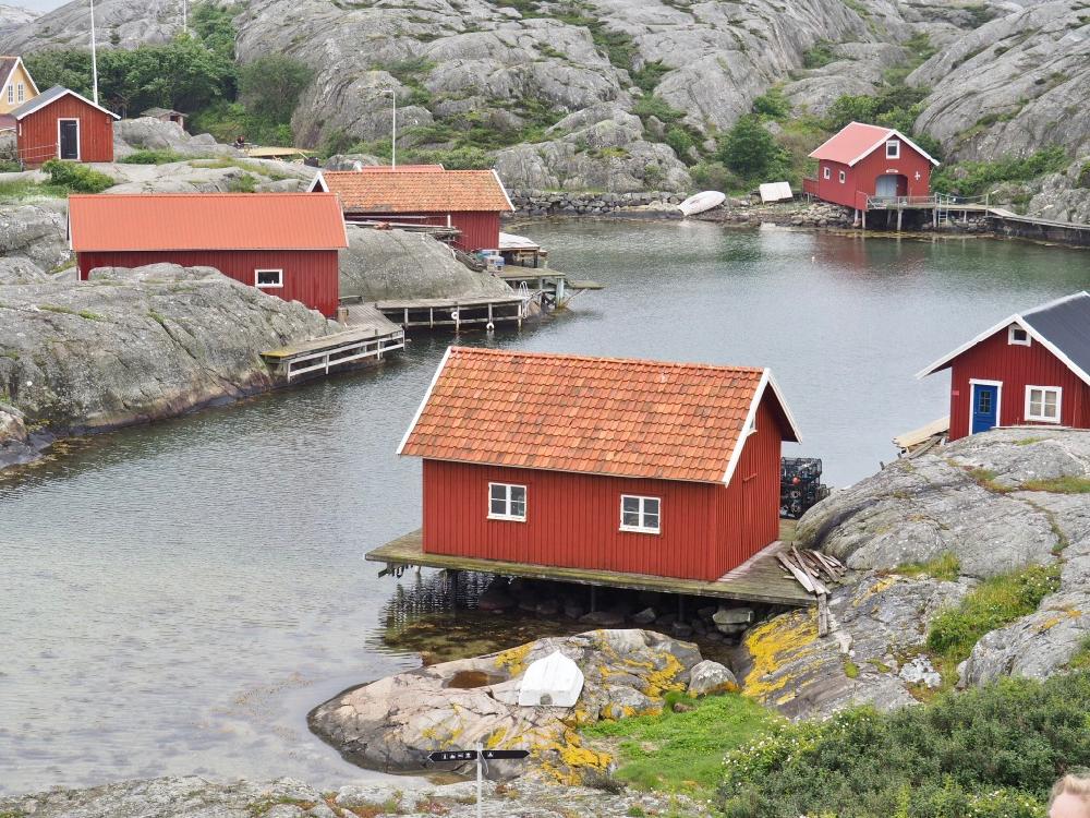Rode houten huizen aan het water bij rotseilandjes