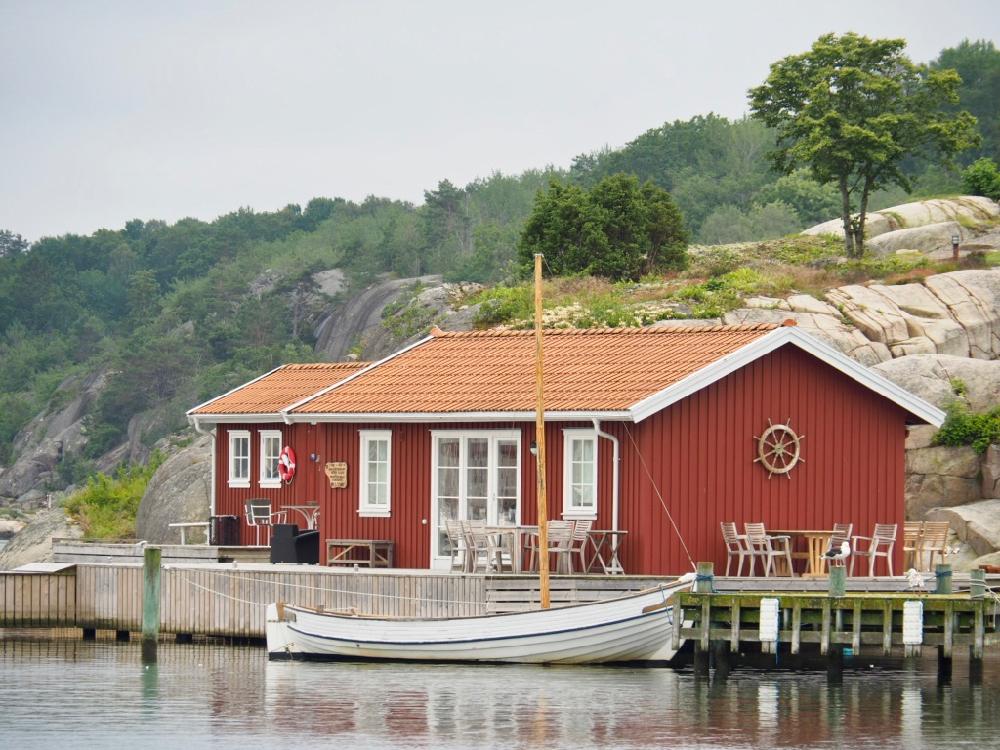 Zweeds houten rood huis aan de waterkant met witte boot ervoor