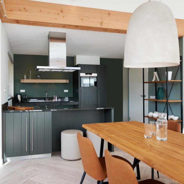 Zwarte keuken met stoeren houten tafel