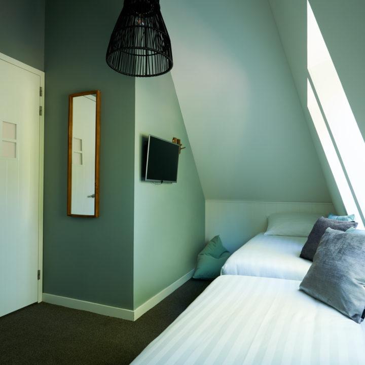 Slaapkamer onder een schuine wand met twee losse bedden