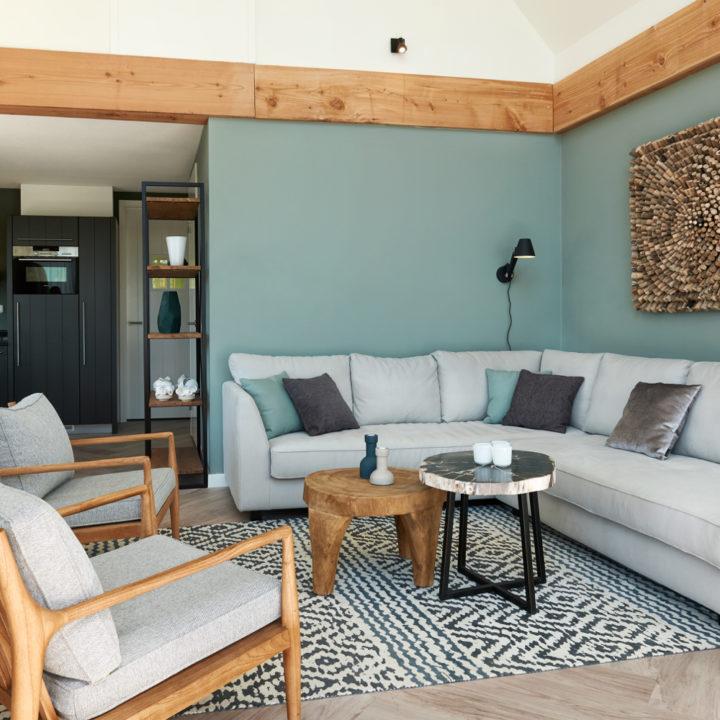 Woonkamer met lichtgrijze muur, zitbank met kussens en zwart-wit vloerkleed