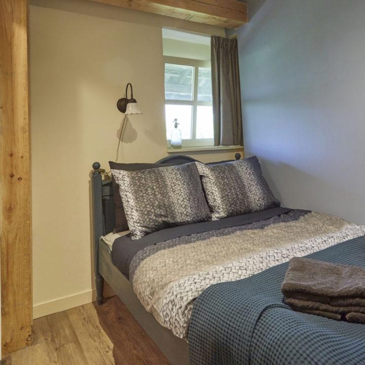 Opgemaakt bed met sprei en stapeltje handdoeken