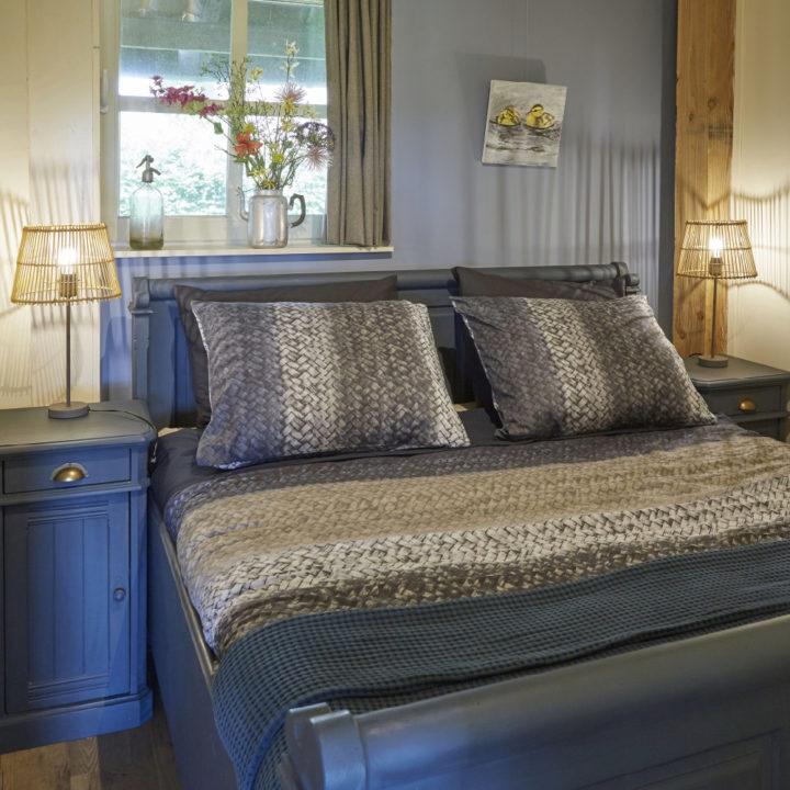 Opgemaakt bed met brandende schemerlampjes ernaast