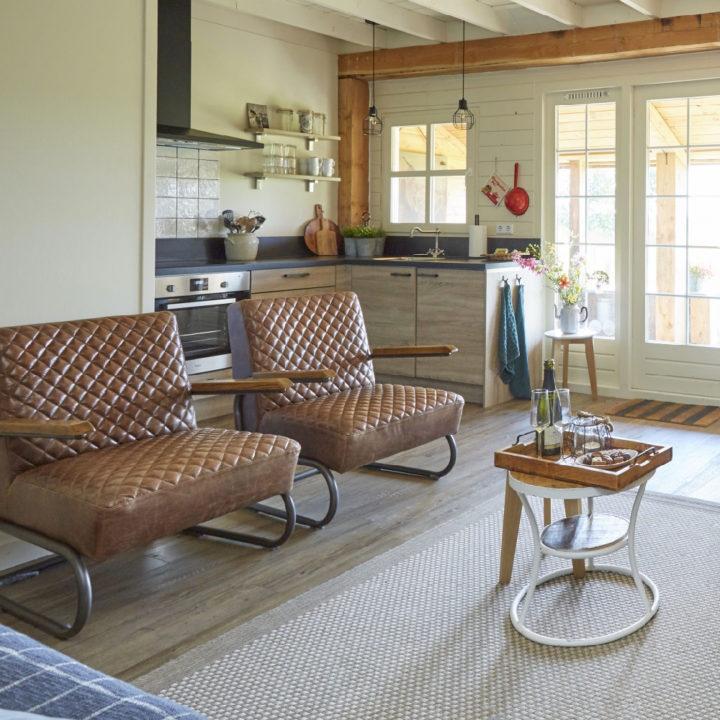 Woonkamer met twee bruine leren fauteuils en zicht op de keuken