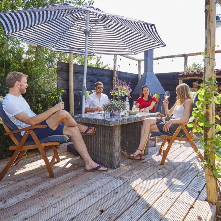 Mensen genieten van een glas wijn in de tuin