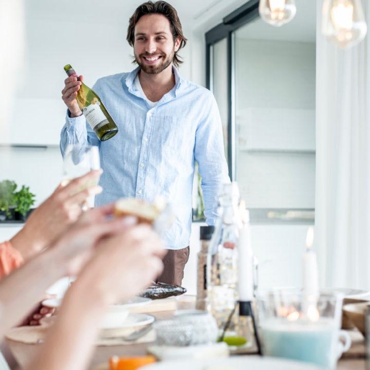 Gastheer met fles wijn aan de eettafel