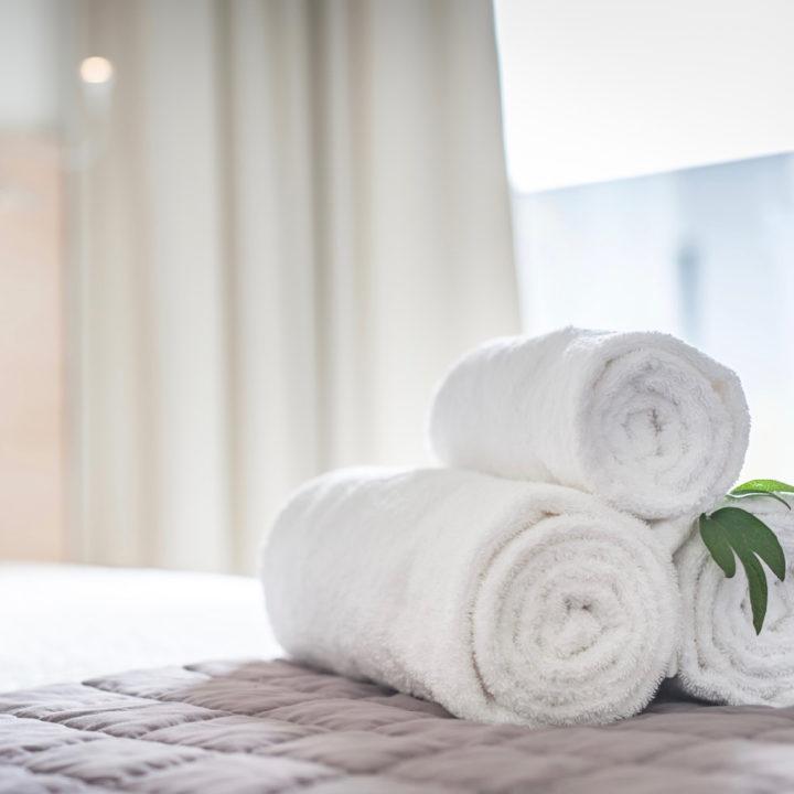 Opgerolde handdoeken op bed