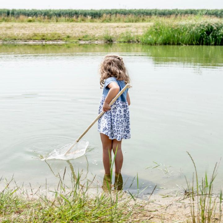 Meisje met schepnet in het water