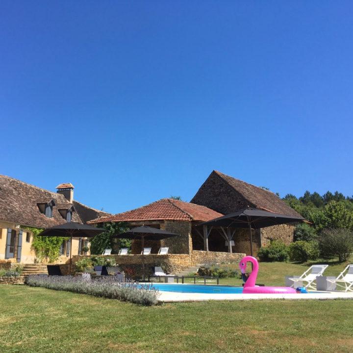 Zwembad met authentieke vakantieboerderij op de achtergrond