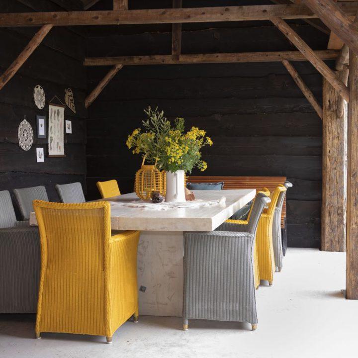 Terras met grote tafel en gekleurde stoelen