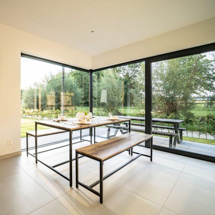 Stalen eethoek met houten blad voor metersgrote ramen
