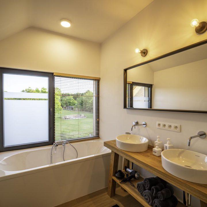 Badkamer met bad en twee wastafels