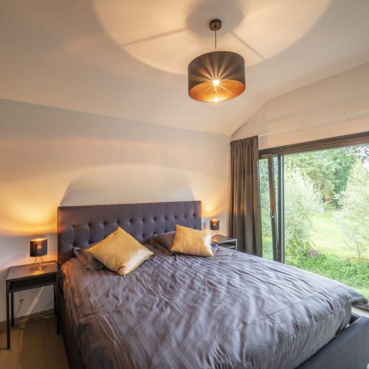 Tweepersoons bed voor een groot raam