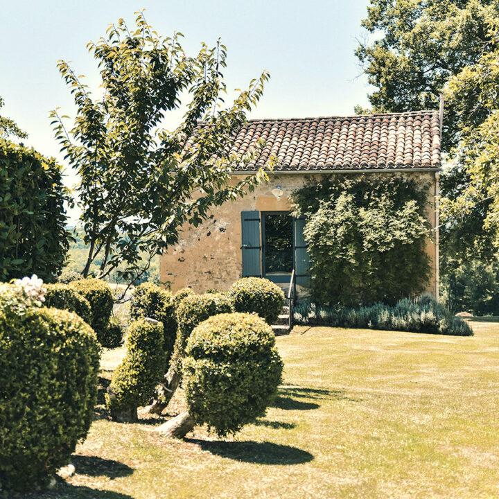 Vakantiehuisje met blauwe luiken in een weelderige tuin
