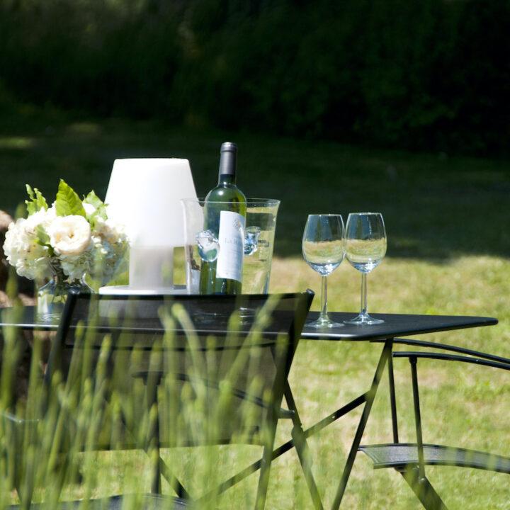Wijnglazen en een wijnkoeler op een zwart tafeltje