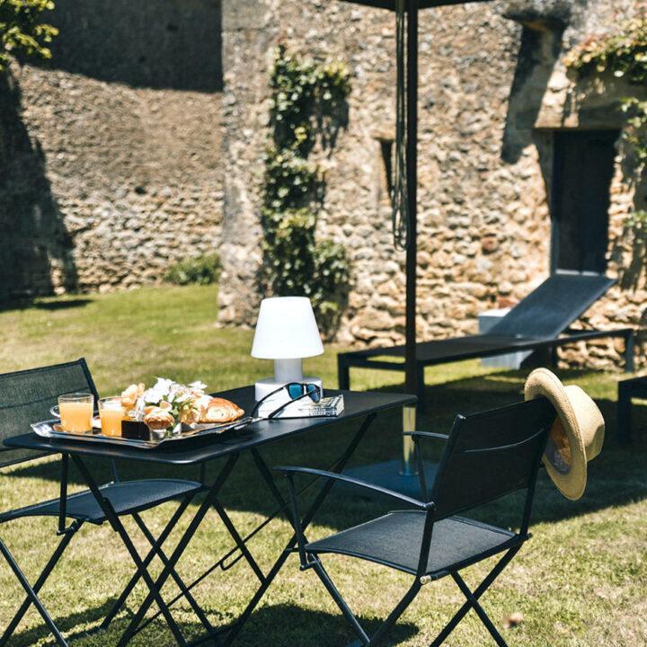 Ontbijt in de tuin met zonnehoedje aan de stoel