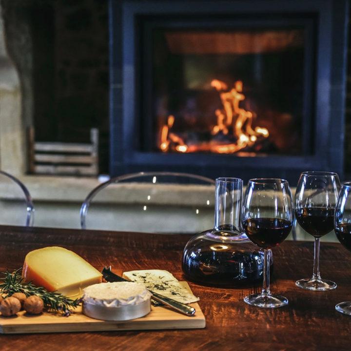 Glazen rode wijn, Franse kaasjes en een brandende haard; genieten in Frankrijk