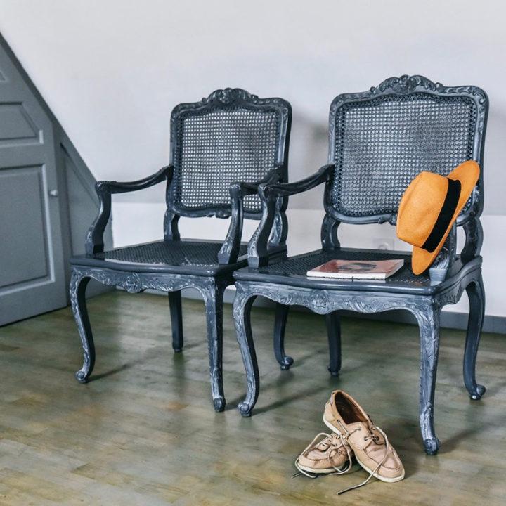 Slaapkamer met twee zwarte stoelen, een paar schoenen en een hoedje