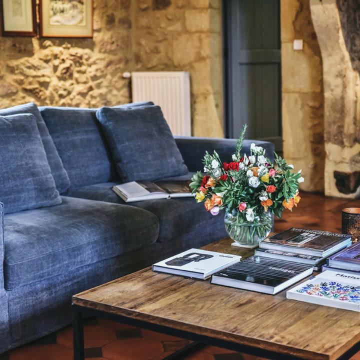 Woonkamer met salontafel vol boeken en een boeket bloemen