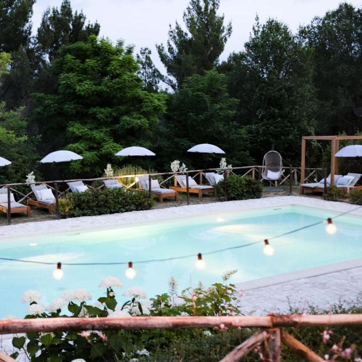Zwembad met verlichting en ligstoelen