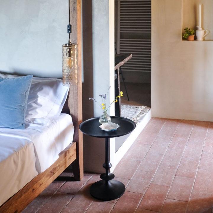 Slaapkamer met zwart tafeltje met bloemen naast het bed