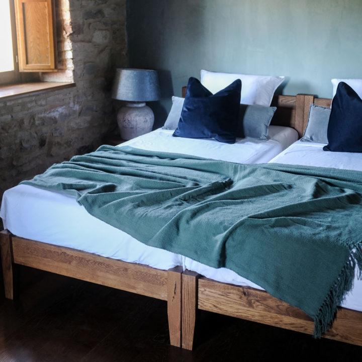 Tweepersoons bed met donkergroene sprei, luxe hotelkamer in Umbrië