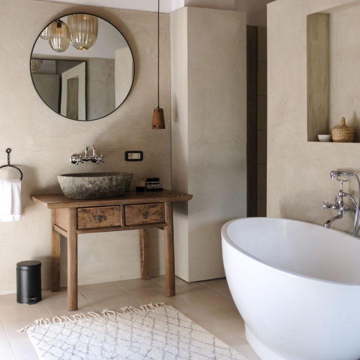 Vrijstaand bad in een badkamer in leemkleuren