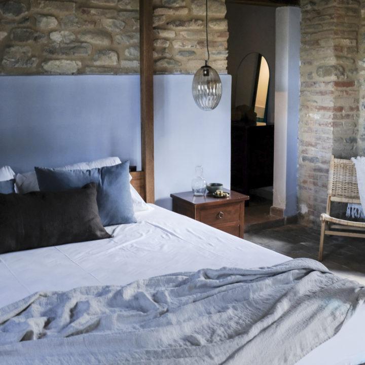 Warme blauwe tinten en stoere muren in een hotelkamer in Umbrië