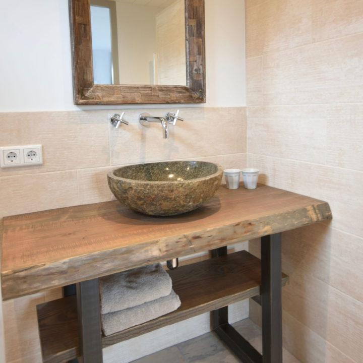 Badkamer met stoere wastafel en robuust houten blad