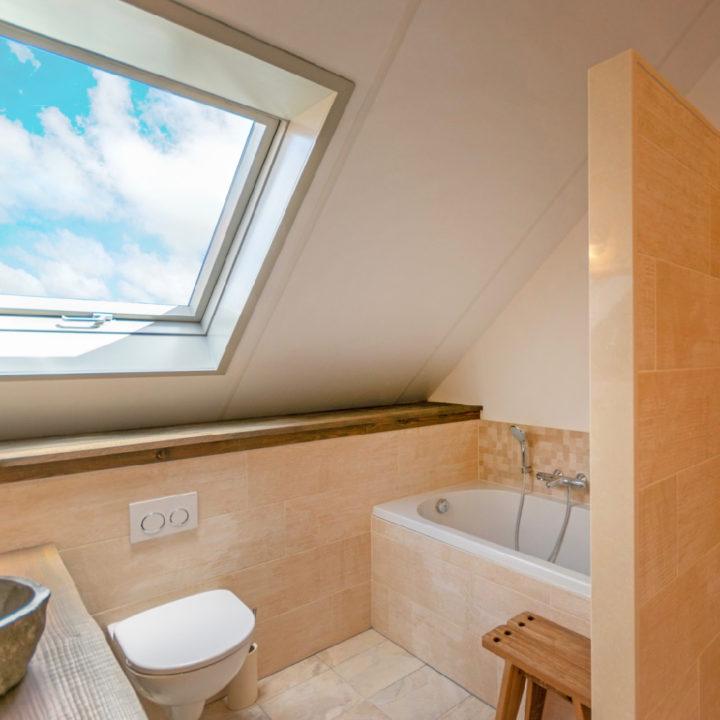 Badkamer met ligbad en dakraam