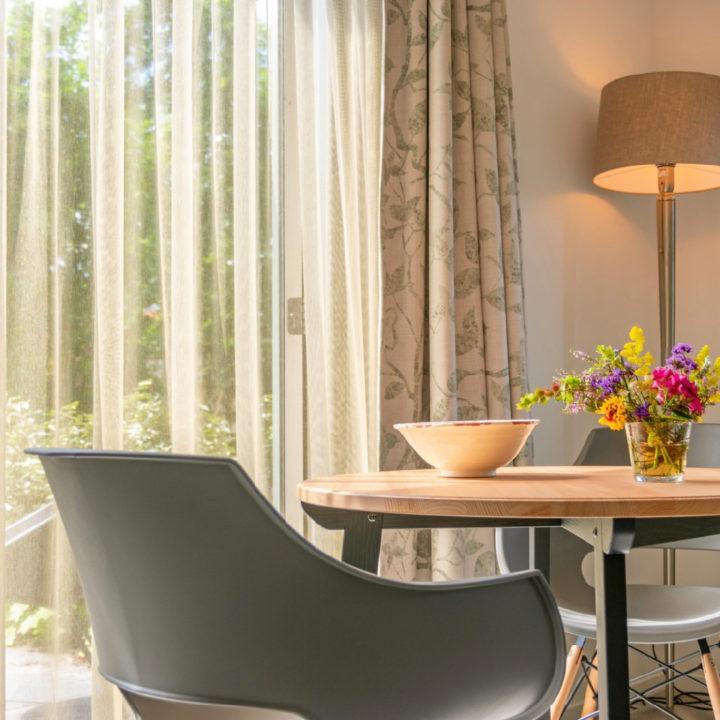 Ronde tafel met kuipstoelen en vaasje bloemen