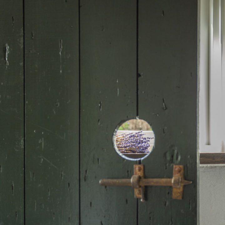 Kijkje door een houten deur met zicht op lavendel