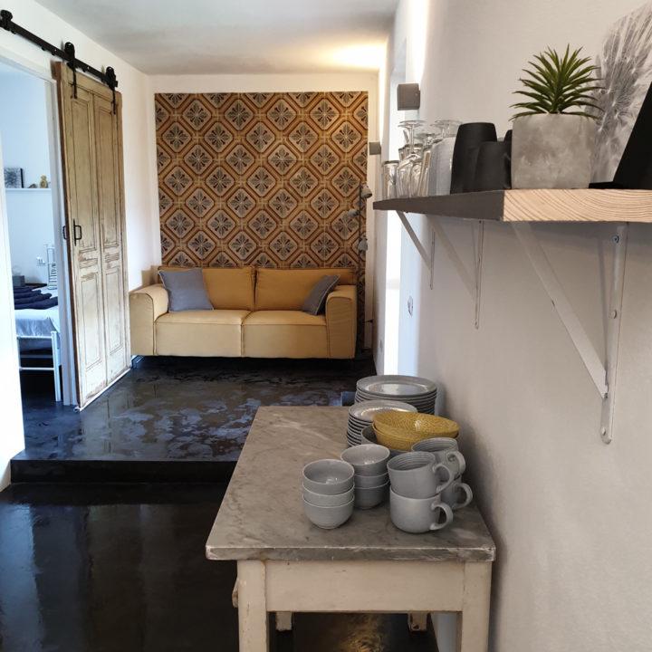 Brocante tafeltje met servies en zithoek op de achtergrond