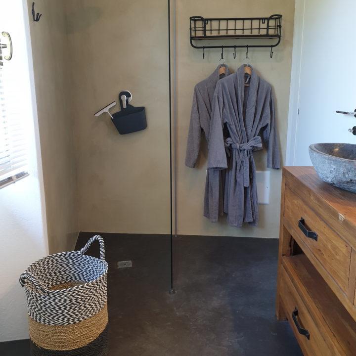 Grijze badjassen en rieten mand in de badkamer van gastenverblijf in de Piemonte