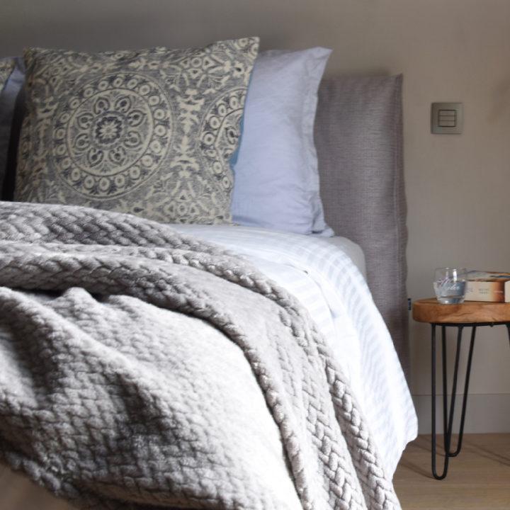 Grijze sprei met luxe kussens op bed in de B&B kamer