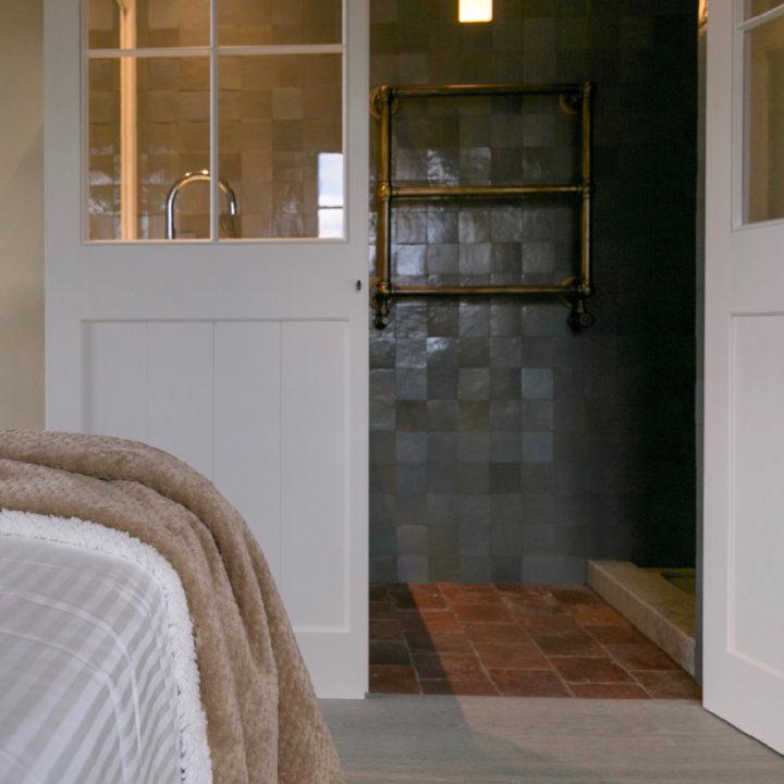 Bed met zicht op de badkamer met groene tegeltjes en houten schuifdeur