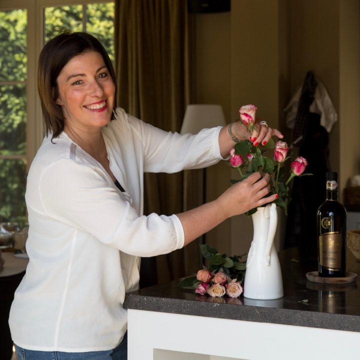 Gastvrouw Isa schikt de bloemen in de vaas