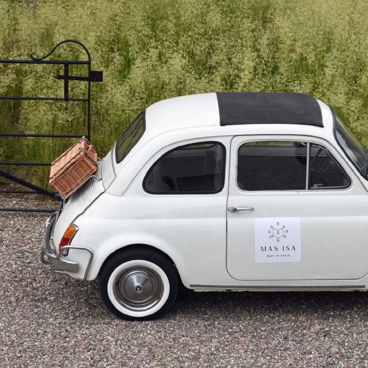 Fiat 500 in het wit, met een rieten koffertje achterop