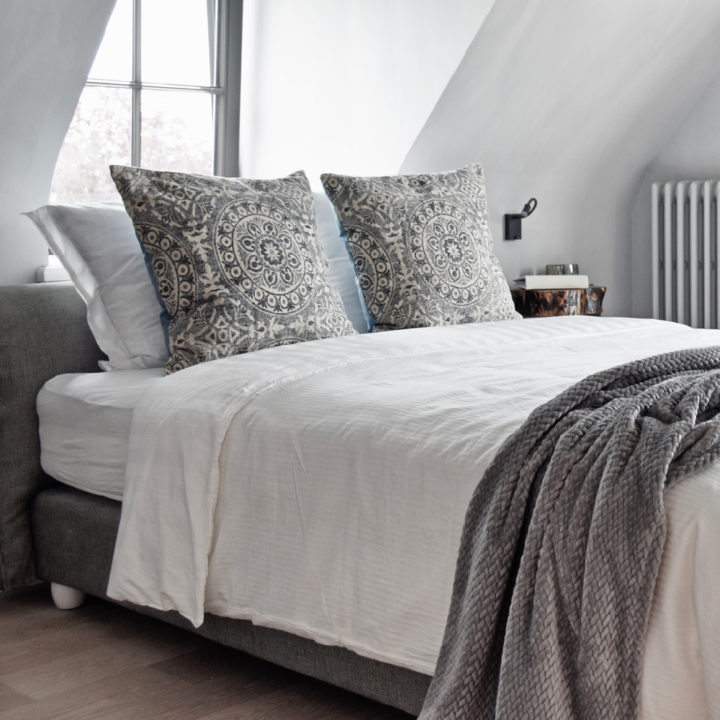 Lichte luxe bed and breakfast kamer met grijze sprei en zacht bedlinnen