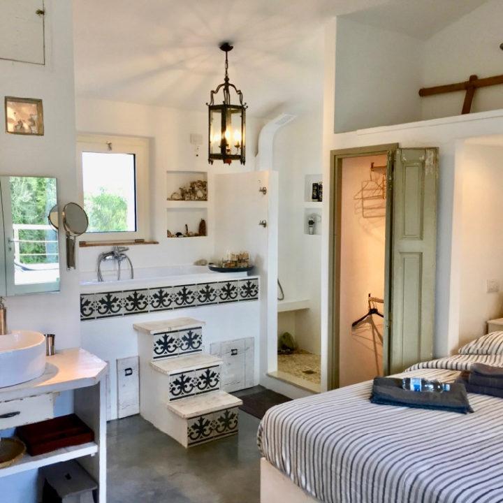 Slaapkamer met open badkamer in een vakantiehuis op Sardinië