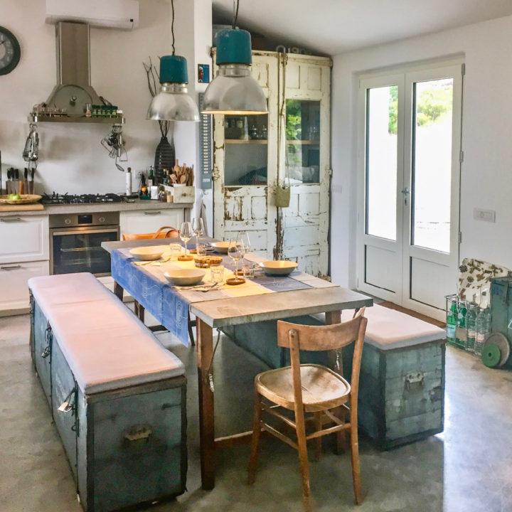 Gedekte tafel met aan weerszijden banken, in een woonkeuken van een vakantiehuis