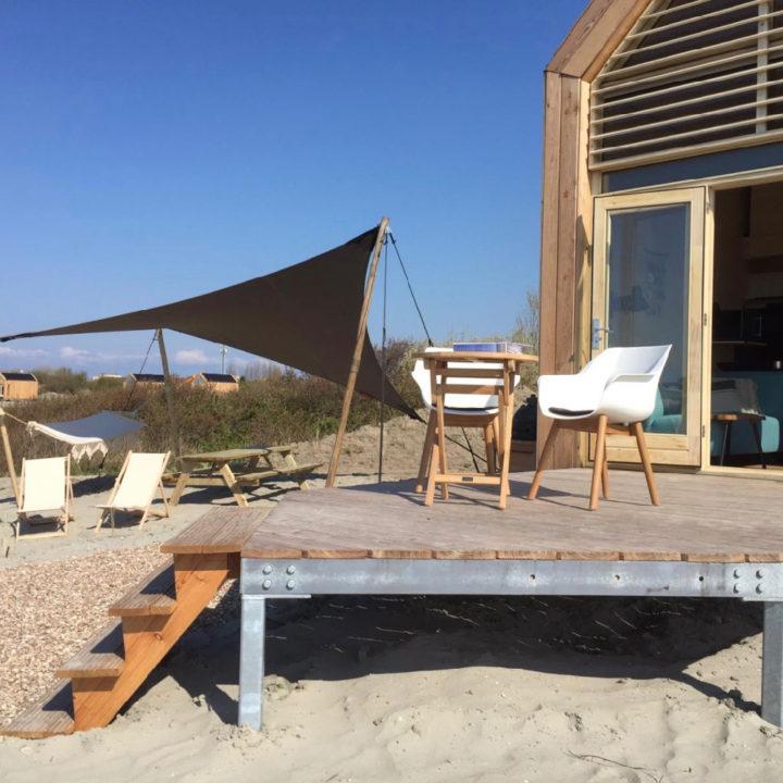 Terras met witte stoelen en een schaduwdoek bij een tiny house op het strand