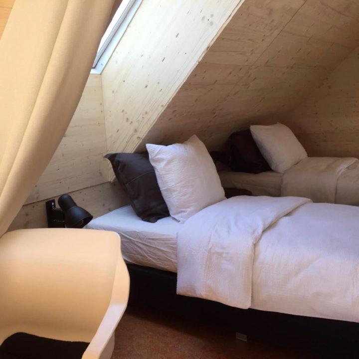 Twee opgemaakte bedden onder een schuin dak