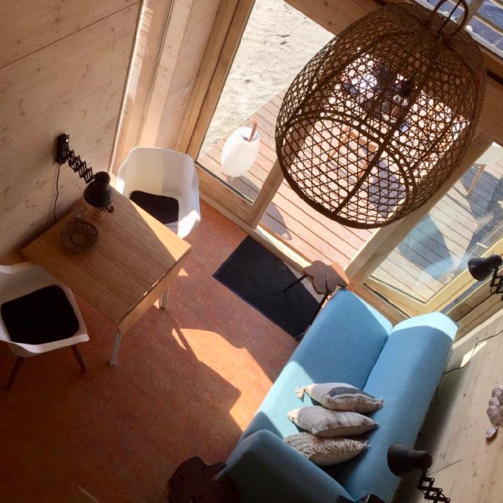 Blauwe bank, zithoekje en rieten lamp in een vakantiehuis