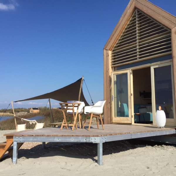 Duurzaam houten vakantiehuis met terras met witte designstoelen